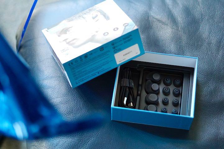 Blaue Soundcore Verpackung liegt auf einem Ledersessel