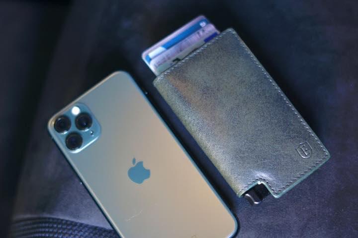 Ekster Parliament Wallet liegt neben einem gruenen iPhone 11 Pro