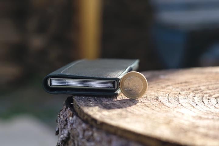 Ekster Slim Wallet liegt auf einem Holzstamm neben einem Eurostueck