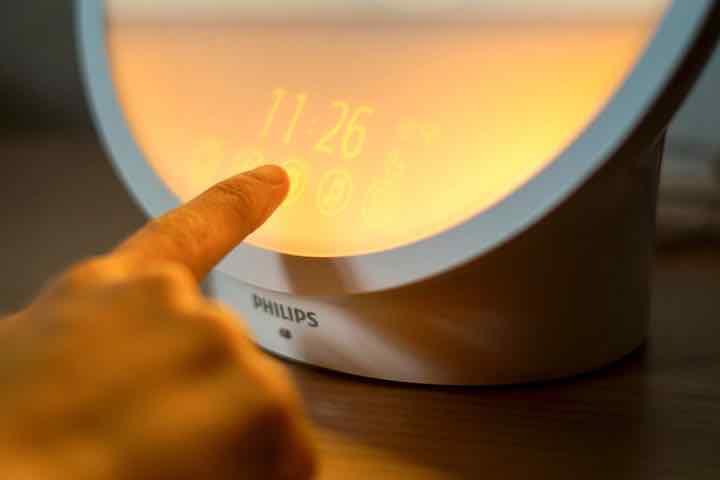Finger tippt auf beleuchtetes oranges Touch Display
