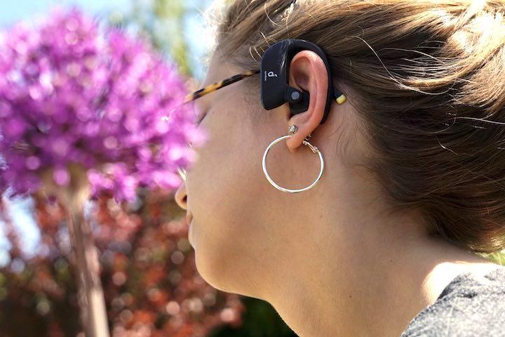 Frau hat Soundcore Headset im Ohr und sitzt vor einer lila Blume