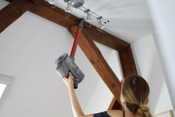Frau saugt mit Handsauger eine Decke ab