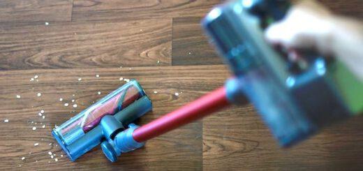 Hand faehrt mit Staubsauger ueber einen Fußboden mit Dreck