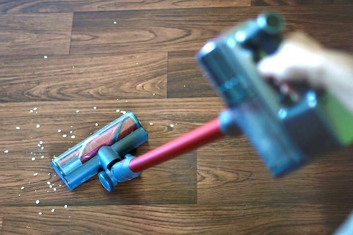 Hand faehrt mit Staubsauger ueber einen Fu%C3%9Fboden mit Dreck