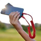 Hand haelt Ladekabel und iPhone gegen die Sonne 160x160