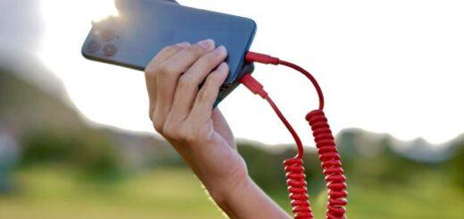Hand haelt Ladekabel und iPhone gegen die Sonne 520x245