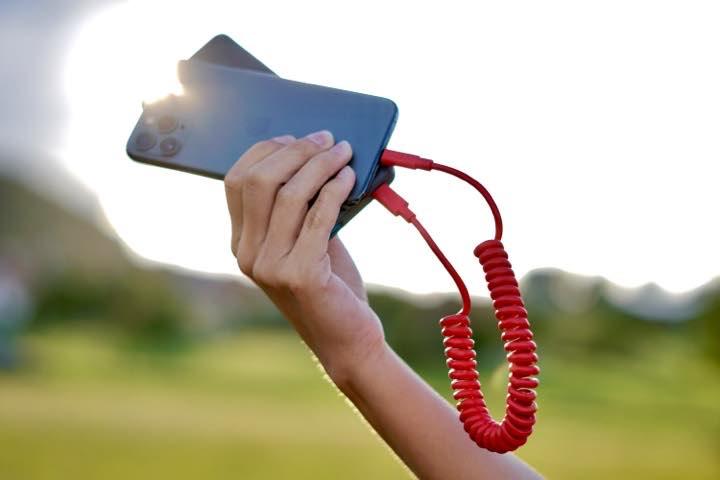 Hand haelt Ladekabel und iPhone gegen die Sonne