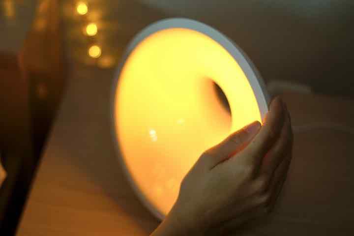 Hand schaltet Philips Lampe mit warmem Licht an