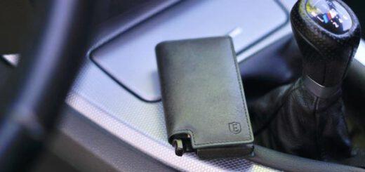 Kleiner Geldbeutel liegt in einem Auto neben einem Schaltknauf