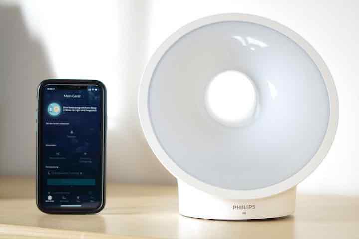 Sleep Mapper App auf iPhone steht neben einer Lampe von Philips