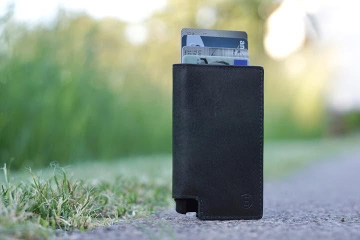Slim Wallet mit Chip Karten steht auf einem Gehweg vor einer gruenen Wiese