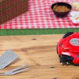 Grillbot auf Tisch mit Grillbesteck und Getränk 160x160