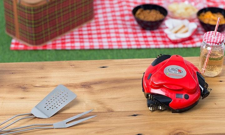 Grillbot auf Tisch mit Grillbesteck und Getränk