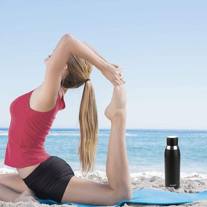 Daway Trinkflasche am Strand neben Sportlerin