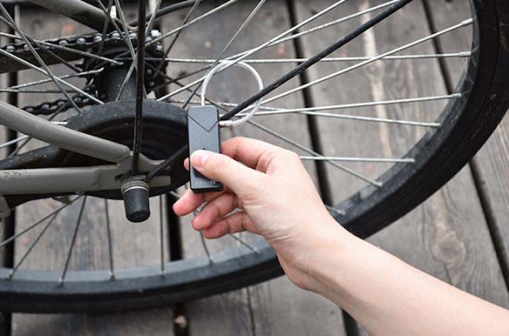Hand öffnet Fipilock an Fahrrad