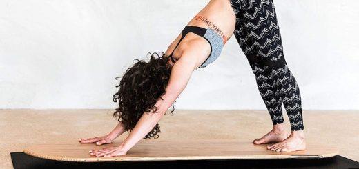 Frau beugt sich auf Yogaboard 520x245