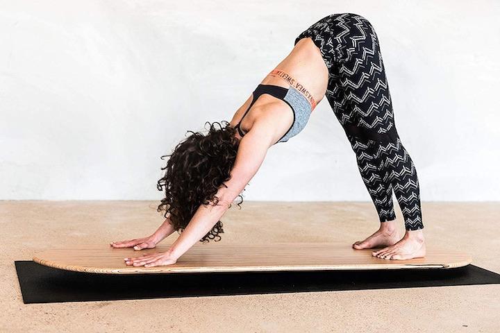 Frau beugt sich auf Yogaboard