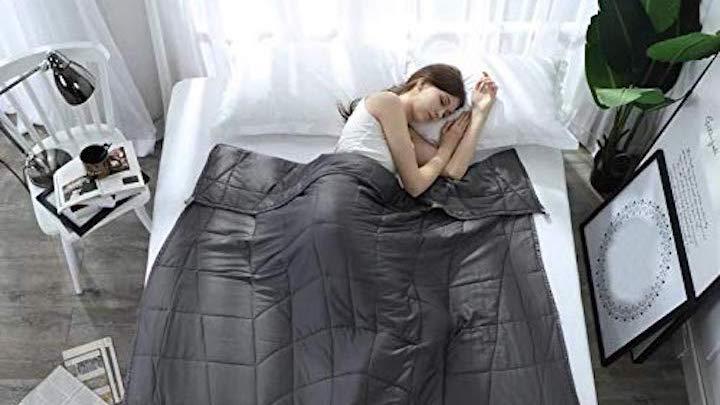 Frau liegt im Bett unter der Esee Home Gewichtsdecke