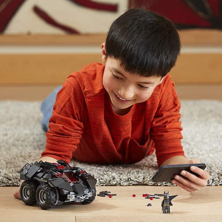 Junge spielt mit Lego Batmobil