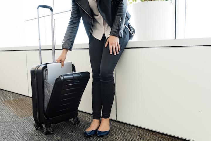 Frau öffnet Frontfache des SkyValet Luggage