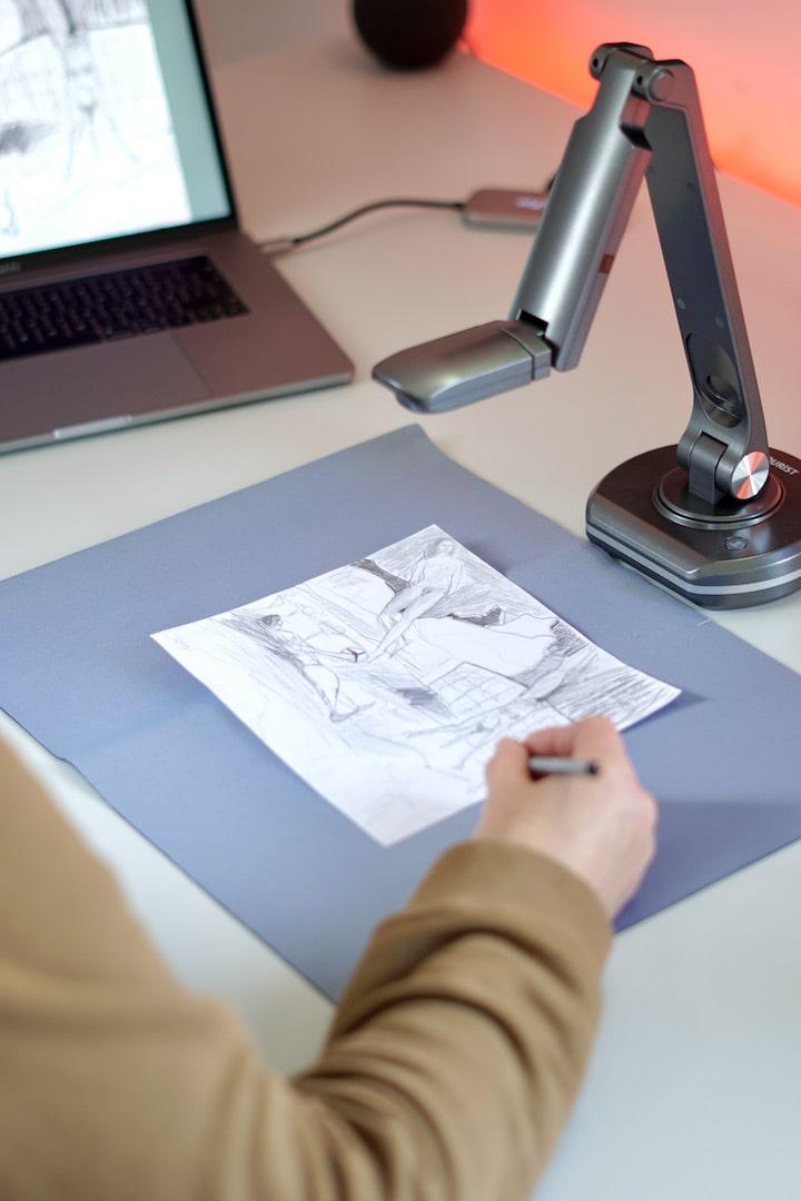 Hand zeichnet ein Bild unter einem Dokumentenscanner
