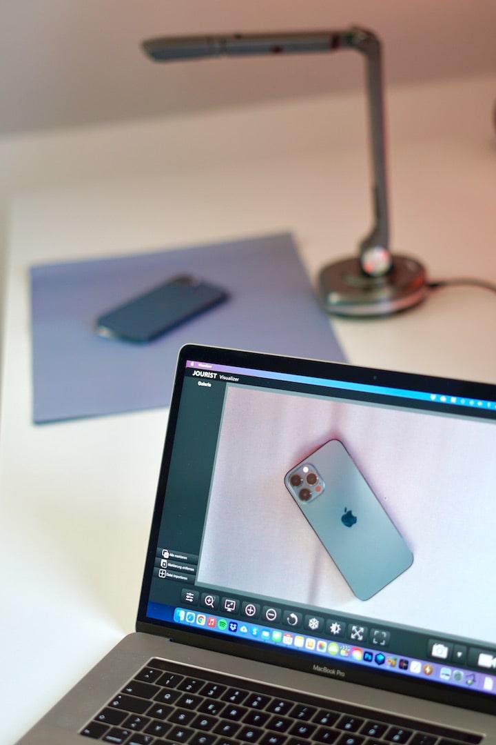 MacBook Pro mit iPhone und Dokumentenscanner im Hintergrund