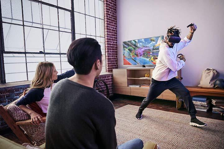 Mann spielt mit Oculus Quest vor Fernseher
