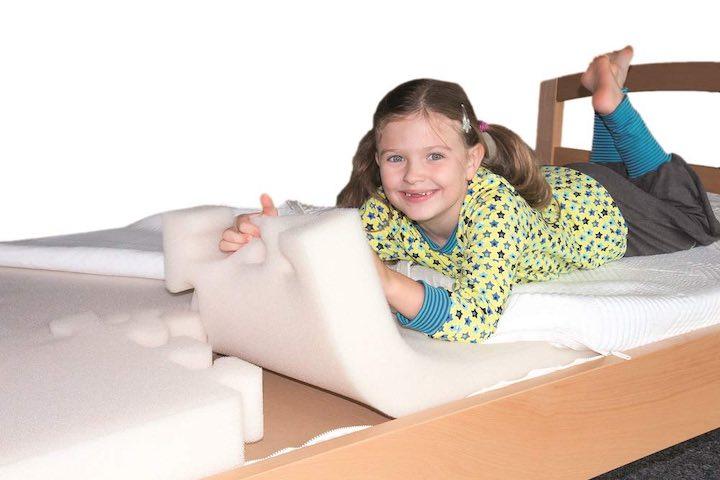 Kind liegt auf Schaumstoff Matraze aus Puzzleteilen