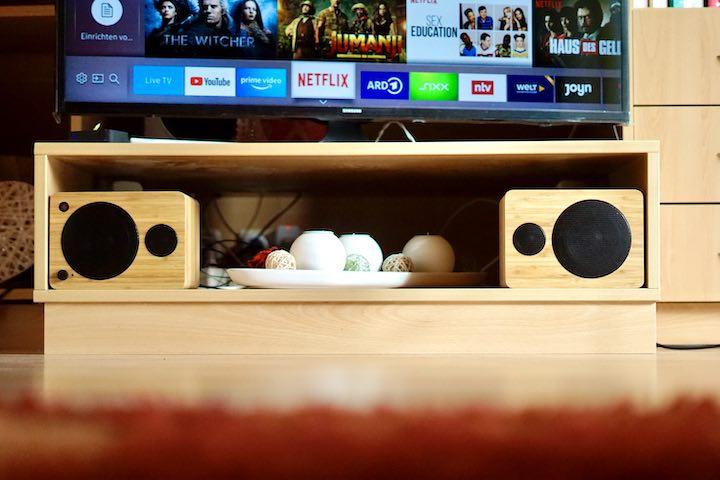 zwei Lautsprecher liegen unter einem Fernseher