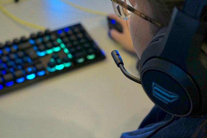 Frau hat ISY IC 6000 Gaming Headset an und sitzt vor einer Tastatur