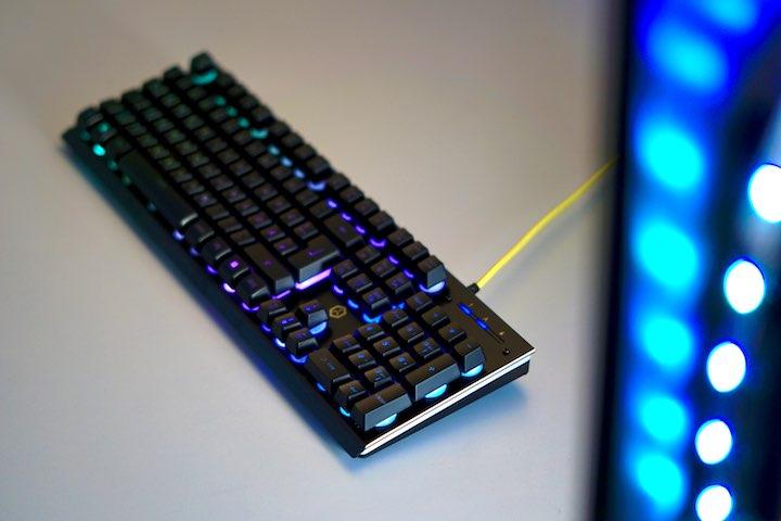 Gaming Tastatur liegt auf Schreibtisch vor leuchtendem LED Streifen