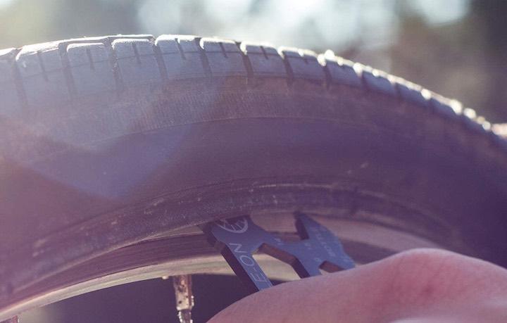 Hand entfernt Reifen von einem Rad mit einem Multifunktionswerkzeug