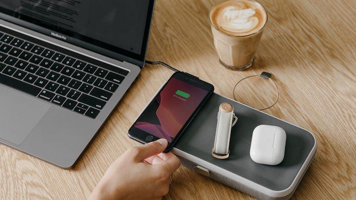Hand legt iPhone auf Organzier neben MacBook und einem Kaffee