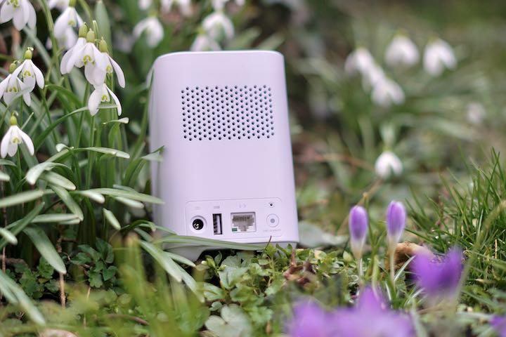 eufyCam 2C Homebase steht auf einer Wiese neben Blumen