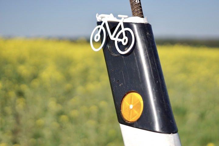 Baiki Gummi Fahrrad Halterung haengt an einem Leitpfosten vor einem gelben Feld