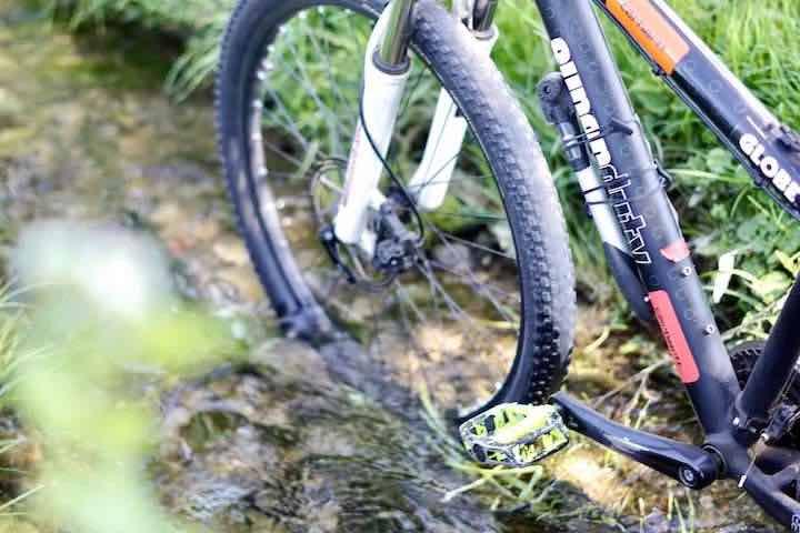 Fahrrad steht mit Fahrradpumpe in Bach
