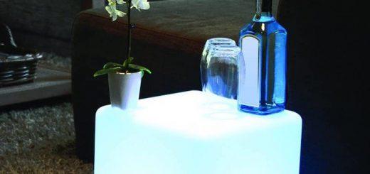 Flasche und Glas stehen auf beleuchtetem LED Würfel in einem Wohnzimmer 520x245