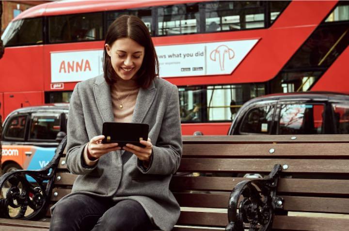 Frau sitzt auf Bank vor Bus und hat Astro Slide 5G Transformer in der Hand