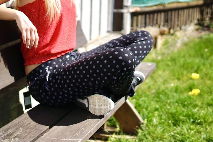 Frau sitzt mit verschraenkten Beinen auf einer Bank auf einer Wiese