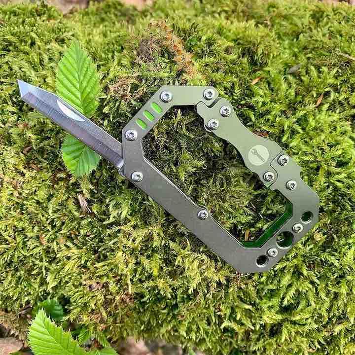 Karabiner mit Messer im Gras