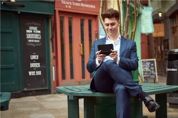 Mann sitzt auf einer Bank und schreibt mit einem Smartphone