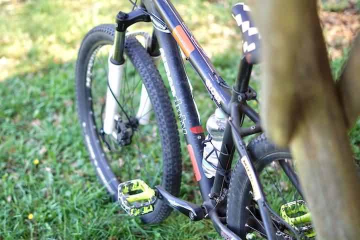 Wasserflasche ist an Fahrrad was auf der Wiese steht befestigt