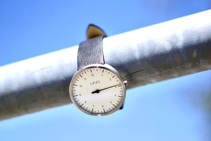 BOTTA Design Uhr Uno haengt an einer Metallstange vor blauem Himmel