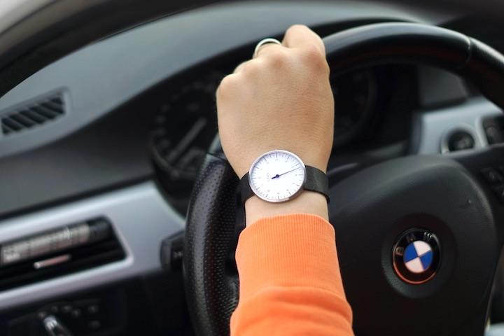 Hand mit Uno Armbanduhr haelt Autolenkrad fest