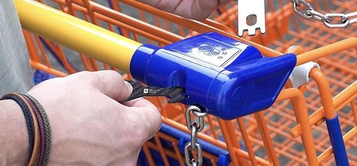 Hand steckt Einkaufswagenloeser in Einkaufwagen