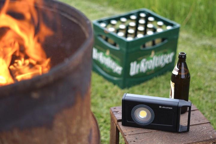 Ledlenser Baustrahler steht neben einem Feuer vor einem Bierkasten