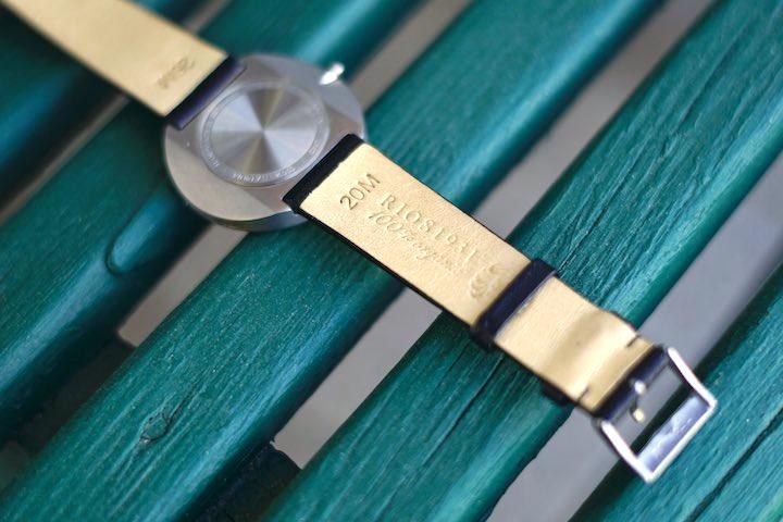 Rueckseite der Design Uhr auf gruenem Holz