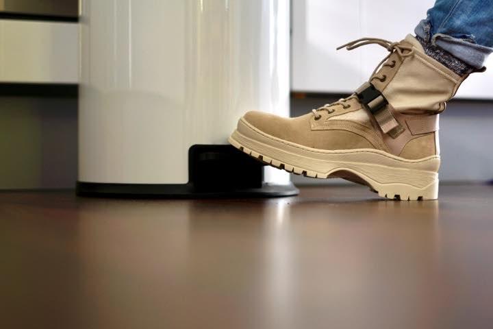 Schuh auf Trittflaeche eines Muelleimers