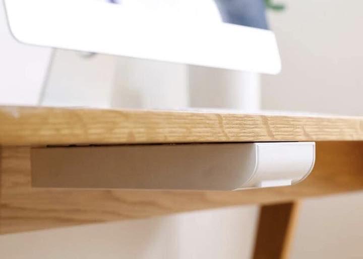 Selbstklebende Schreibtischschublade haengt unter einer Tischplatte