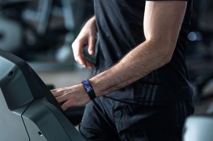 mann im fitnessstudio hat eine smartwatch am arm